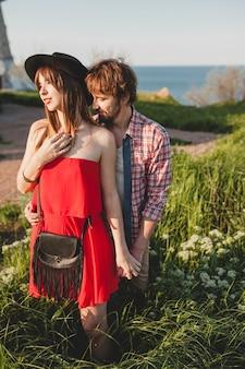 Inschrijving jonge stijlvolle paar verliefd op platteland, indie hipster bohemien stijl, weekendvakantie, zomer outfit, rode jurk, groen gras, hand in hand, glimlachen