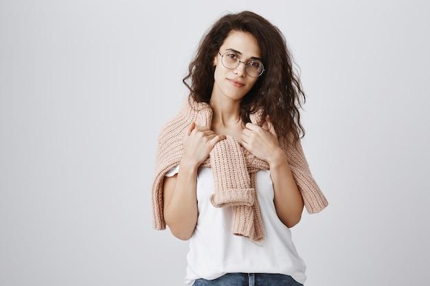 Inschrijving jonge vrouw in glazen met trui om nek gewikkeld