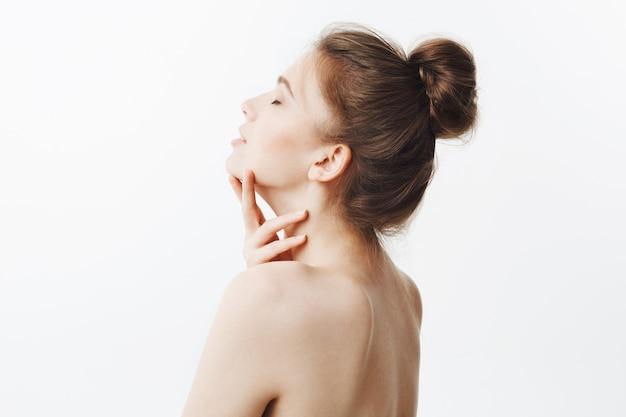 Inschrijving knap europees meisje met donker haar in knot kapsel en benige lichaamstype, poseren met blote schouders, nek aanraken met handen, achterhoofd gooien met gesloten ogen in ontspannen en kalme blik.