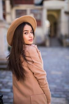 Inschrijving lachende dame loopt op straat en poseren in casual moderne jas en hoed