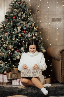 Inschrijving meisje in witte trui opent geschenkdoos zittend op de vloer in de buurt van de kerstboom.