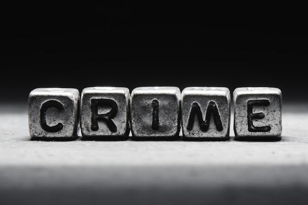 Inschrijving misdaad op metalen blokjes op een zwarte achtergrond
