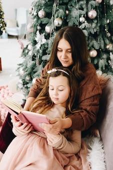 Inschrijving moeder en dochter moment met boek in de buurt van versierde kerstboom Premium Foto