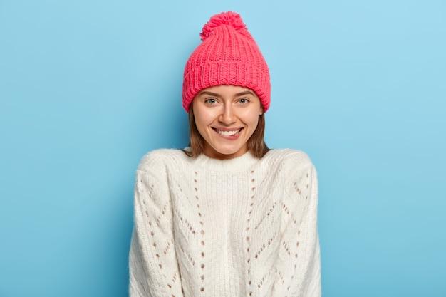 Inschrijving mooi meisje met vrolijke blik, bijt op de lippen, kijkt naar de camera met opgetogen, draagt roze hoed en witte trui, geïsoleerd over blauwe muur, voelt zich comfortabel thuis