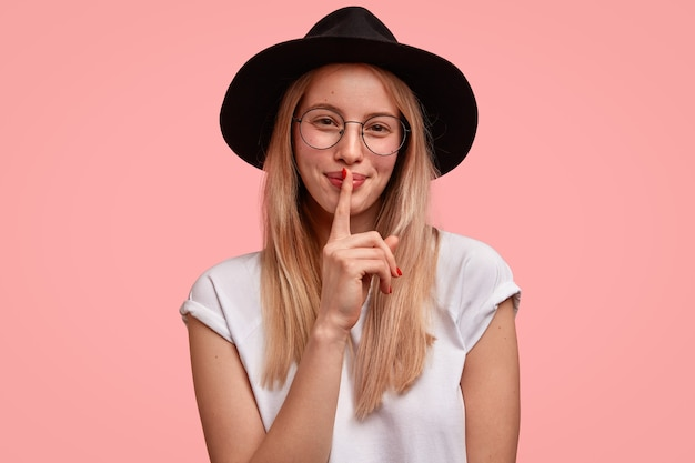 Inschrijving mooie jonge vrouw met tevreden uitdrukking, stilte gebaar maakt, kijkt gelukkig en zegt shh