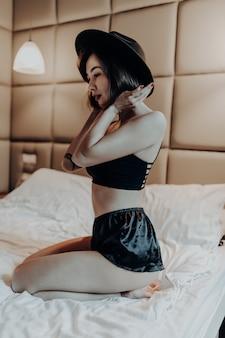 Inschrijving mooie vrouw in mode-ondergoed en hoed zitten op het bed in de ochtend