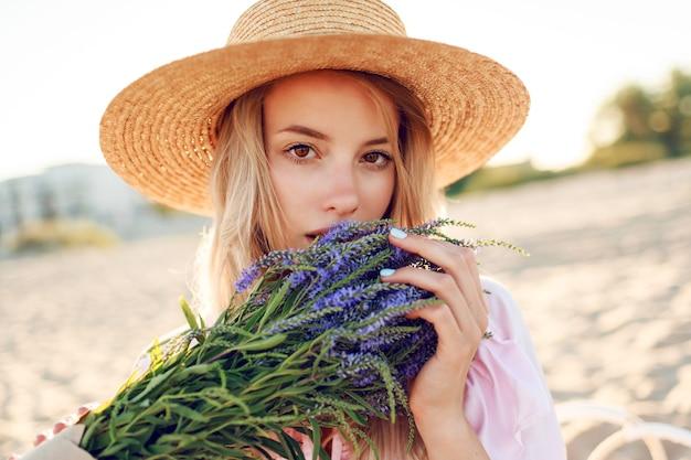 Inschrijving mooie vrouw in strohoed poseren op zonnig strand in de buurt van de oceaan met boeket bloemen. portret close-up.
