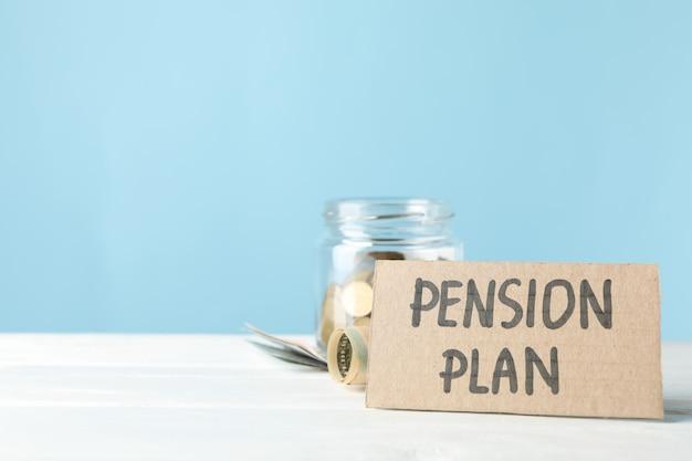 Inschrijving pensioenplan en pot met geld tegen blauwe oppervlakte