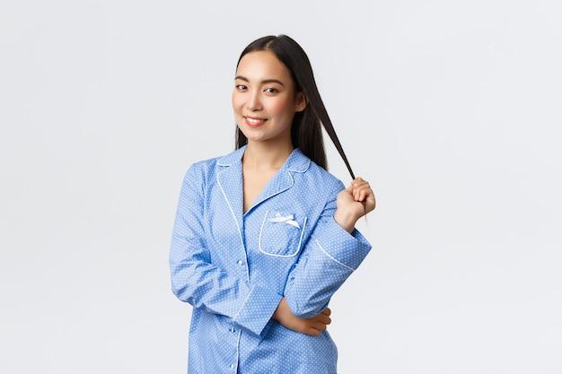 Inschrijving prachtig aziatisch meisje glimlachend dromerig op camera, staande in blauwe pyjama's op witte achtergrond. vrouw bereidt zich voor, ga slapen in jammies, breng huidverzorgingsproducten aan voor het slapengaan