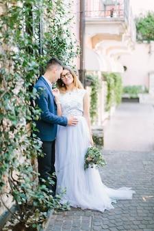 Inschrijving romantisch jong koppel in blauwe kleding lopen bij zonnig weer, zoenen en knuffelen. jong bruidspaar in sirmione, italië