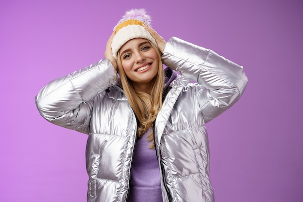 Inschrijving romantische aantrekkelijke blonde vrouw genieten van wintersport ski resort met plezier kijken tevreden glimlachend breed kantelend hoofd aanraken hoed dragen zilveren stijlvolle jas, paarse achtergrond.
