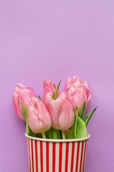 Inschrijving roze tulpen binnenkant rood gestreepte popcorn cup op pastel violette achtergrond. plat leggen. kopieer ruimte. plaats voor tekst. concept van internationale vrouwendag, moederdag, pasen. valentijnsdag liefdesdag