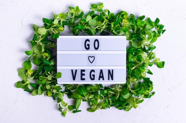 Inschrijving veganistisch in een frame van groene maïssalade op een witte gestructureerde achtergrond