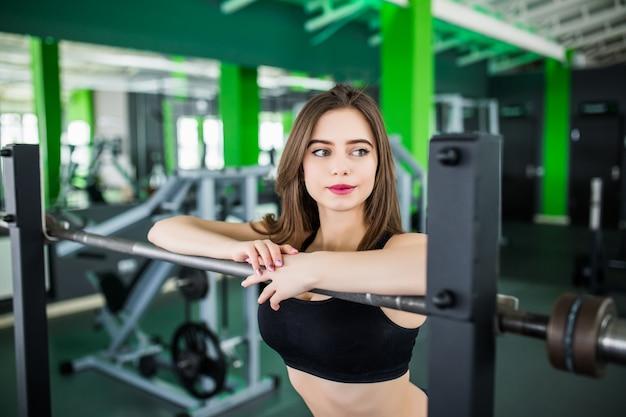 Inschrijving vrouw met lang donkerbruin haar en grote ogen poseren in modern fitnesscentrum in de buurt van de spiegel in korte sportkleding