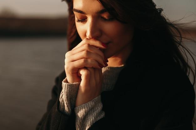 Inschrijving vrouw verwarmende handen dichtbij meer in de herfst
