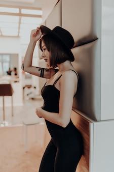 Inschrijving vrouw volwassen brunette vrouw in zwarte jurk en hoed staande in de buurt van de muur in luxe appartement