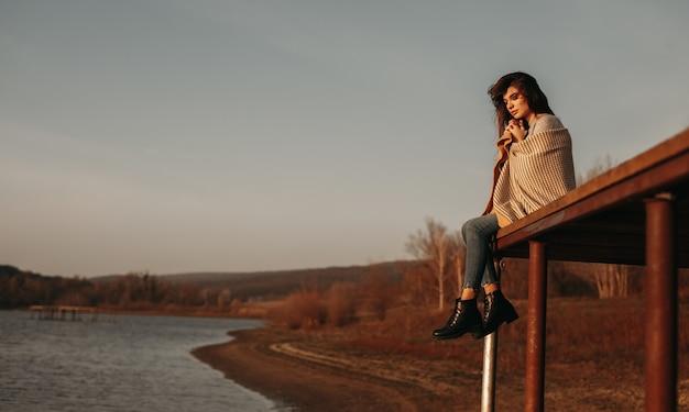 Inschrijving vrouw zittend op pier in de buurt van vijver bij zonsondergang