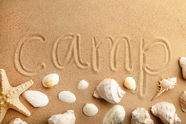 Inschrijvingskamp met schelpen op strandzand
