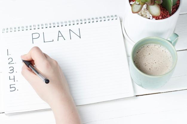 Inschrijvingsplan in blocnote, close-up, hoogste mening, concept planning, doel het plaatsen