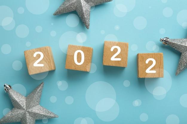 Inscriptie 2022 met zilveren sneeuwvlokken op blauwe achtergrond. bovenaanzicht