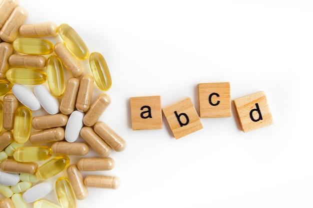 Inscriptie abce in houten kubussen op een witte achtergrond van verschillende pillen