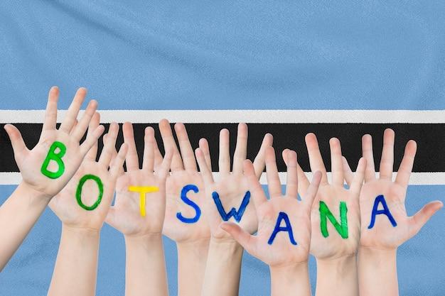 Inscriptie botswana op de handen van de kinderen tegen een wapperende vlag van botswana
