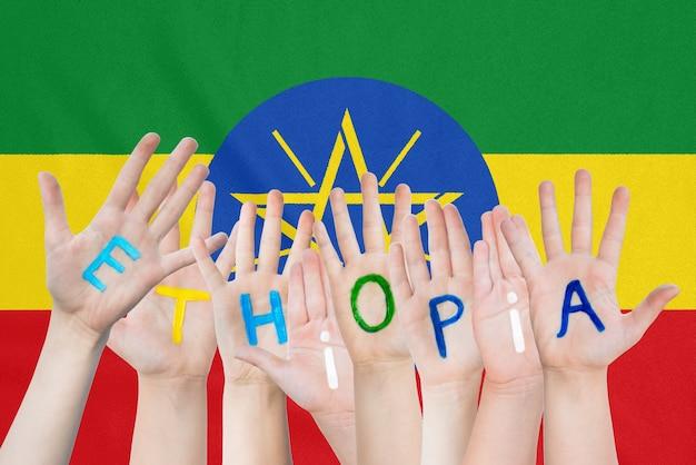 Inscriptie ethiopië op de handen van de kinderen tegen de achtergrond van een wapperende vlag van ethiopië