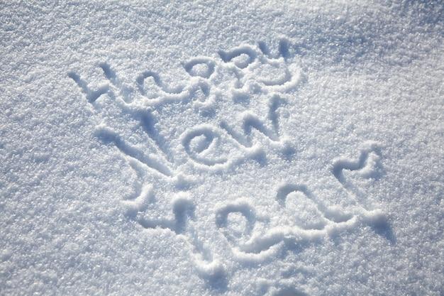 Inscriptie gelukkig nieuwjaar op besneeuwde winter achtergrond