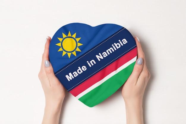 Inscriptie gemaakt in namibië de vlag van namibië. vrouwelijke handen met een hartvormige doos.