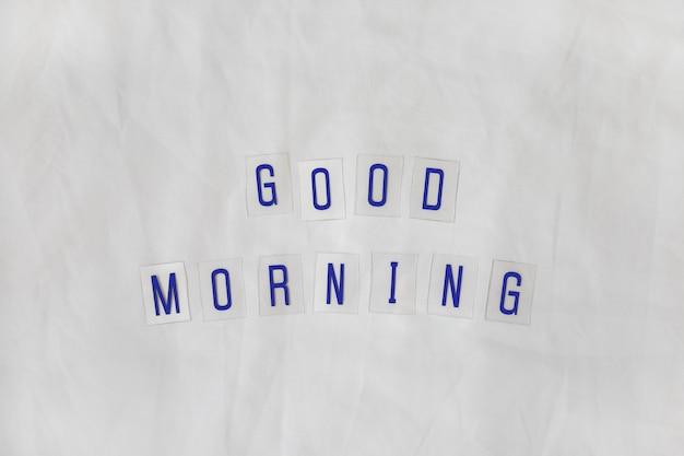 Inscriptie goedemorgen, samengesteld uit donkerblauwe letters op doorzichtige plastic bases op wit
