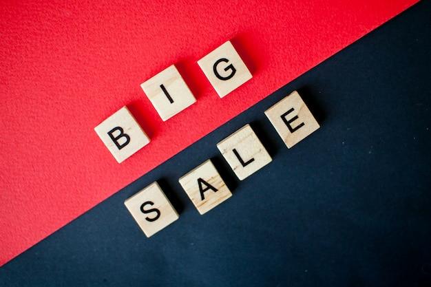 Inscriptie grote verkoop van houten blokken op een zwarte en rode achtergrond