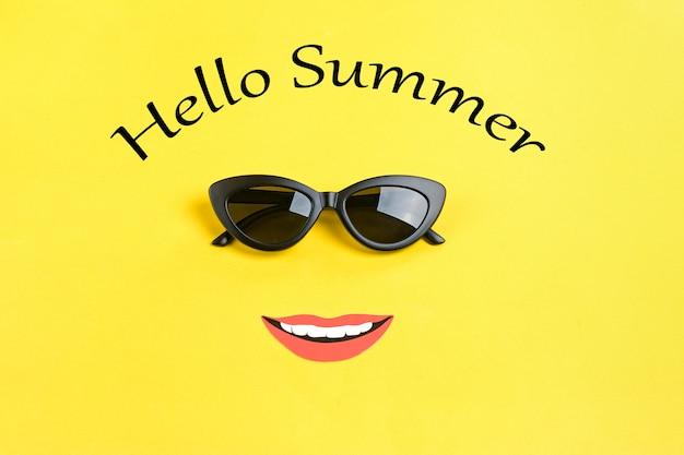 Inscriptie hallo zomer de zon met stijlvolle zwarte zonnebril, lachende mond op geel