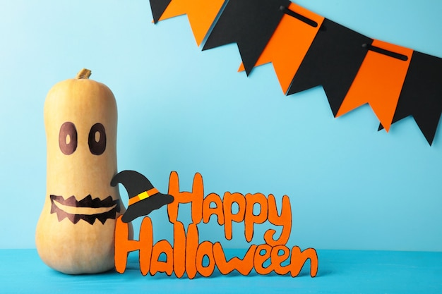 Inscriptie happy halloween met pompoen op blauwe achtergrond