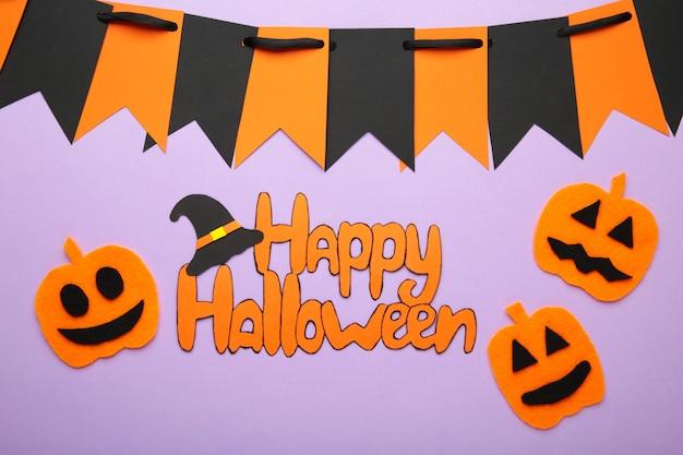 Inscriptie happy halloween met pompoenen op paarse achtergrond. bovenaanzicht