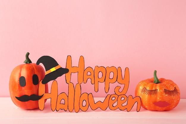 Inscriptie happy halloween met pompoenen op roze achtergrond. bovenaanzicht