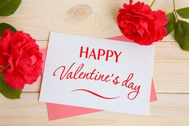 Inscriptie happy valentine's day, rode rozen en een kaart