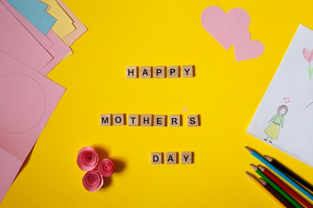 Inscriptie happy womens day bekleed met houten letters plat leggen kinderachtig tekening voor moederdag naast potloden