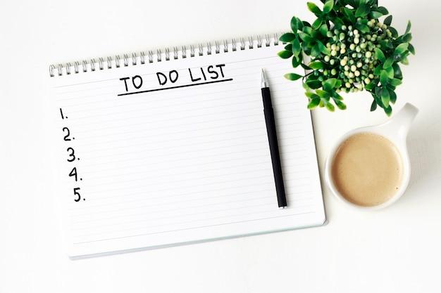 Inscriptie in een notitieblok. takenlijst en kopje koffie
