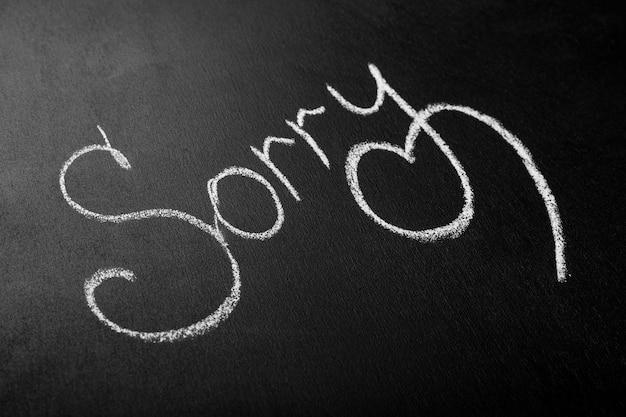 Inscriptie in wit krijt op een zwart bord sorry het concept van een verontschuldiging vragen