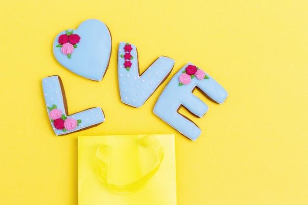 Inscriptie liefde door zelfgemaakte koekjes en gele pakket met kopie ruimte. concept vakantie voedsel. plat lag met pastelkleuren.