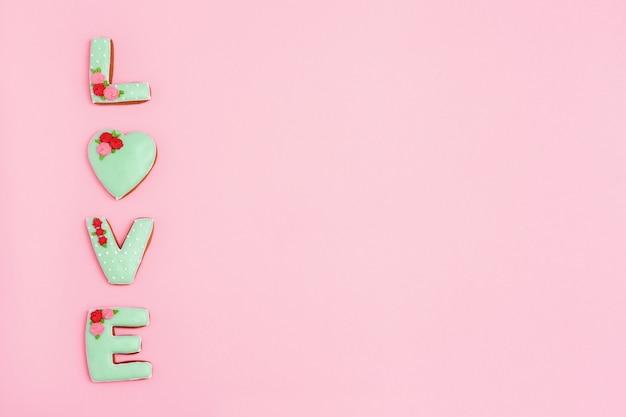 Inscriptie liefde door zelfgemaakte koekjes op roze achtergrond met kopie ruimte. concept vakantie voor bruiloft of valentijnsdag. minimale stijlsamenstelling.