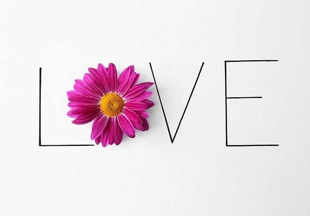Inscriptie liefde met roze bloem op witte achtergrond