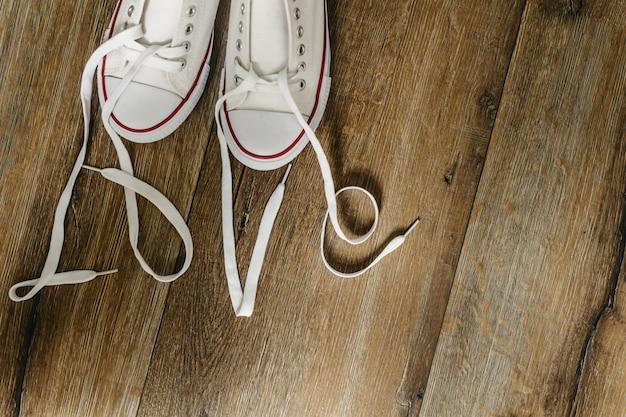 Inscriptie liefde met veters op schoenen. originele valentijnsdagliefde. houten vloer .