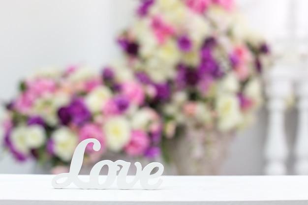 Inscriptie liefde op een achtergrond van bloemen. vrije ruimte. kopieer ruimte.