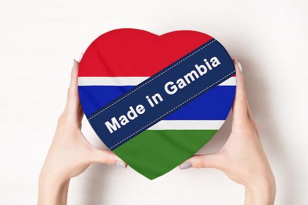Inscriptie made in gambia, de vlag van gambia. vrouwelijke handen met een hartvormige doos. .