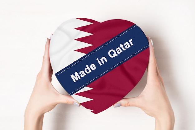 Inscriptie made in qatar de vlag van qatar. vrouwelijke handen met een hartvormige doos. .