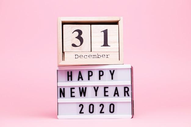 Inscriptie op een witte doos met achtergrondverlichting met kalender van kubussen met de inscriptie 31 december