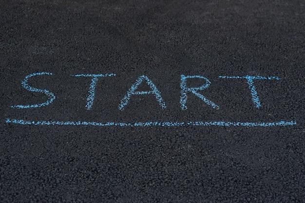 Inscriptie op het asfalt start. let op op de stoep. laat het hoofd zakken en lees het belangrijke bericht.