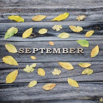 Inscriptie september op een houten ondergrond, frame van gele bladeren