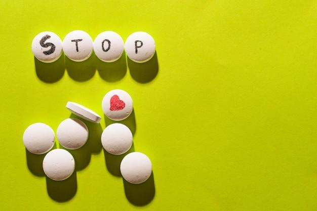 Inscriptie stop gemaakt van witte medische pillen op een heldergroene ruimte